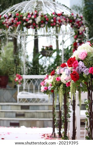 Floral Arrangement on Wedding Aisle with Gazebo in Background