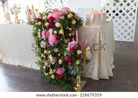 Shutterstock Floral arrangement to decorate the wedding feast, the bride and groom. Flowers, candles, a bottle of champagne. The vintage.