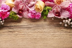 Floral arrangement with orchids, roses and carnations on wooden background, copy space.