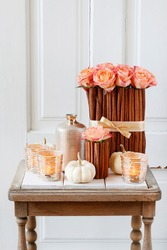 Floral arrangement with roses and cinnamon sticks stands on the table.