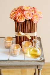 Floral arrangement with roses and cinnamon sticks stands on the table, small golden candle holders are by it's side.