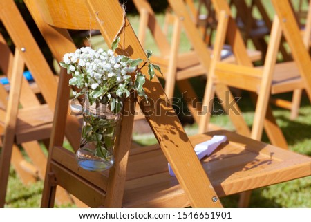 Floral arrangements on chairs at an outdoors wedding #1546651901