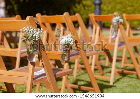 Floral arrangements on chairs at an outdoors wedding #1546651904