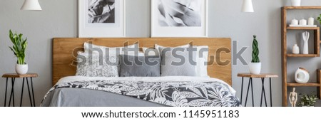 Floral bedclothes on double bed with wooden headboard standing in real photo of bedroom interior with two posters and fresh plants #1145951183