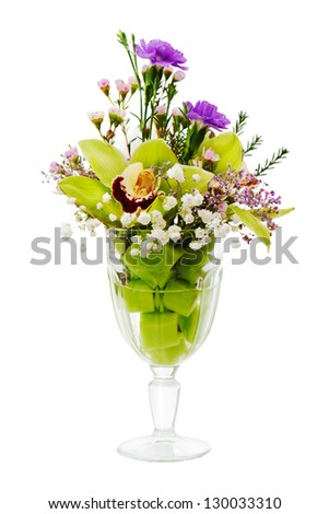 Floral bouquet of orchids, roses and carnation arrangement centerpiece in glass vase isolated on white background