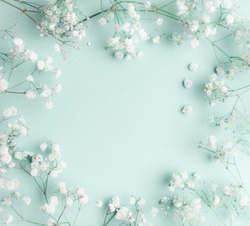 Floral composition with light, airy masses of small white flowers on turquoise blue background, top view, frame.  Gypsophila Baby's-breath flowers