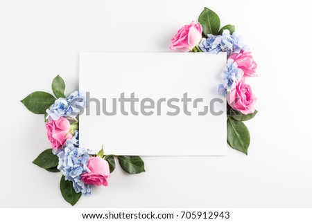 floral composition with roses, hydrangea flowers and blank card, isolated on white