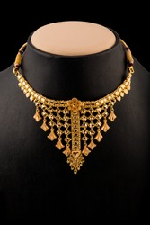 Floral design cool gold neckless isolated on black background.