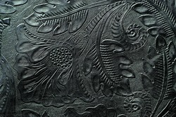 Floral design embossed to black leather with hand tools for leather tooling - close up.