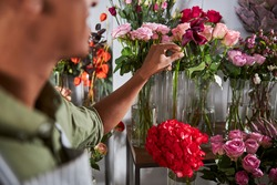 Floral designer standing next to the table with flower vases and getting a single flower out of the water