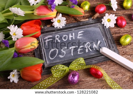 Floral easter background with handwritten german easter greetings Old black board decorated with tulip flowers daisies easter eggs and green bow