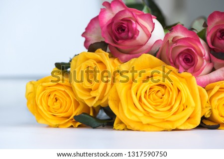 Floral festive background from a large bouquet of flowers. Close-up of delicate pink and sunny yellow roses on a white table. Love theme. Celebration.