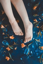 Floral flat lay with woman legs, yellow flowers, and glass smithereens from a broken vase. Conceptual photography