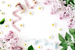 floral frame with lilac flower, chamomile, fresh branches and spool with blue and beige ribbon isolated on white background. flat lay, top view