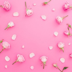 Floral frame with roses flowers and petals on pink background. Flat lay, Top view. Valentines day background