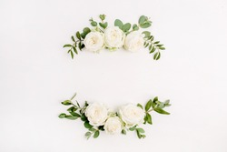 Floral frame wreath made of white rose flower buds on white background. Flat lay, top view blog hero header mockup.