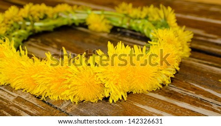 Floral garland made of yellow flowers laying on top of an old wooden table
