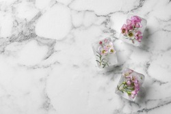 Floral ice cubes on marble background, top view. Space for text
