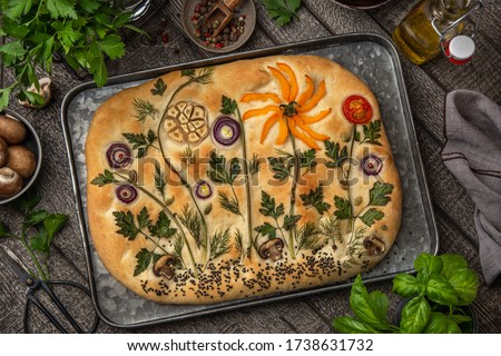 Floral painting focaccia,  garden flatbread art, food trend. Old wooden background, top view