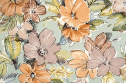 Floral pattern on fabric. Brown and orange flowers print as background.