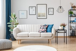 Floral pillow on beige sofa next to table with candles in living room interior with pouf and posters