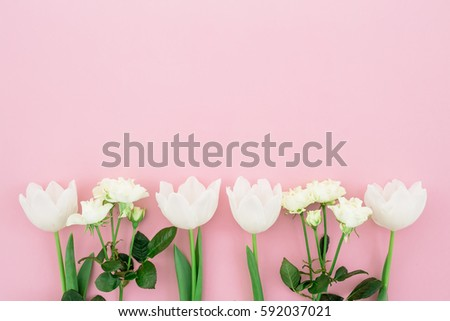 Floral's background. Floral bouquet made of white roses and tulips on pink background. Flat lay, top view. Woman day background. #592037021