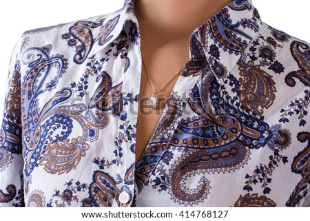 Floral shirt and small pendant. Accessory and shirt on mannequin. Lady's stylish accessory on display. Delicacy and style. #414768127