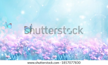 Floral spring natural blue background with fluffy airy lilac flowers on meadow and fluttering butterflies on blue sky background. Dreamy gentle air artistic image. Soft focus.