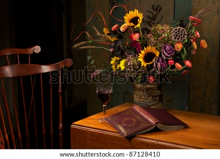 Floral still life with wine and gold embossed leather bound book, on an antique wooden table. Low key, dark background, spot lighting, and rich Old Masters colors. Horizontal format  and copy space.