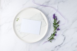 Floral wedding invitation card mockup. Blank paper postcard, vintage envelope on white plate and bunch lavender flowers with ribbon on light marble background. Top view with copy space