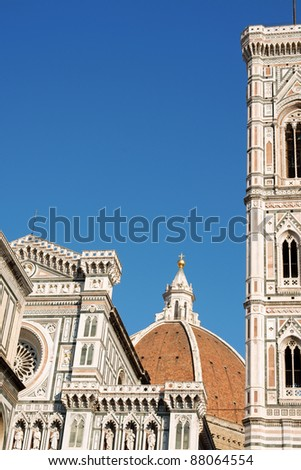Florence Cathedral of Santa Maria del Fiore or Duomo di Firenze, detail of the facade, Brunelleschi's dome and Giotto's bell tower against the blue sky. - stock photo