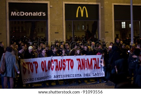 "FLORENCE, ITALY - NOVEMBER 27: Animal right demonstration in front of McDonald's with banner ""Stop animal holocaust"" against the company McDonald's on November 27, 2011 in Florence (Italy)"