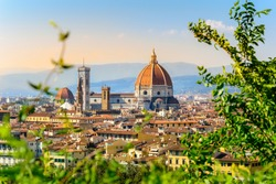 Florence, Italy: scenic view on Florence old town with Duomo Cathedral of Santa Maria del Fiore and Giotto's Bell Tower from Michelangelo square at sunset with defocused green leaves in front