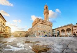 Florence, Italy. View of Piazza della Signoria square with Palazzo Vecchio reflecting in a puddle at sunrise