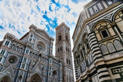 Florence, Toscana-Italy - 24.08.2020: The Cathedral of Florence and the Baptistery of San Giovanni photographed together from below against the blue sky.