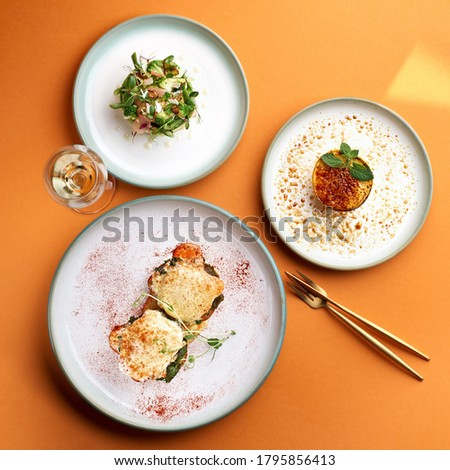 Florentine eggs - poached eggs and a delicious avocado salad, dessert cr me brulee in orange background Photo stock ©