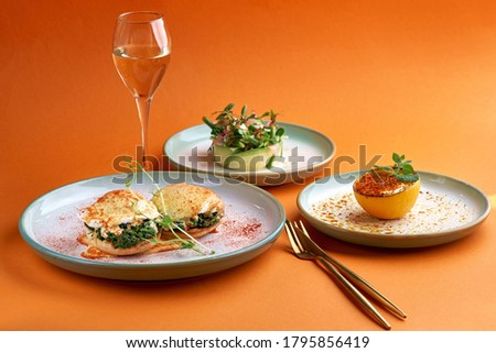 Florentine eggs poached eggs and a delicious avocado salad, dessert cr me brulee in orange background Photo stock ©
