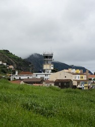 Flores airport tower jutting out from the surrounding landscape, with mist in the mountains on the background. Santa Cruz das Flores, Flores Island.
