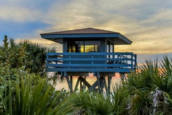 Florida Lifeguard Station framed by green shrubbery and beautiful sunset.