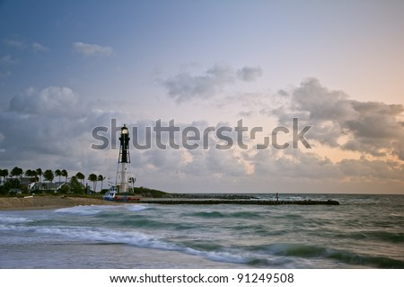 florida's historic hillsboro lighthouse shining at colorful dawn beside the ocean inlet and jetty