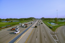 Florida Turnpike at Pompano Beach, Florida with Northbound and Southbound Rush Hour Traffic in Late Afternoon Sun with Clear Blue Sky Above