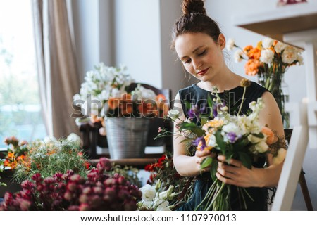 florist arranging a bouquet of beautiful colorful flowers inside her floral shop