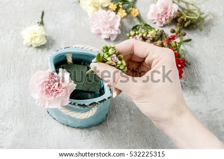 Florist at work: How to make bouquet of pink carnations and yellow Kalanchoe blossfeldiana flowers in blue ceramic vase. Step by step, tutorial.