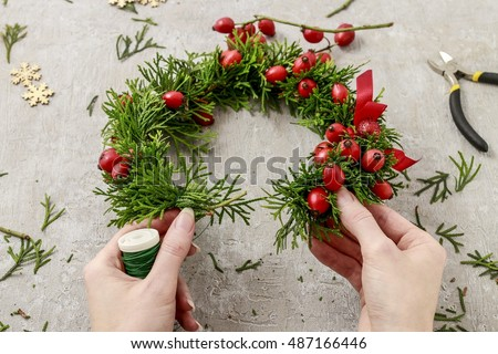 Florist at work: How to make traditional christmas door wreath with thuja twigs and wild rose fruits. Step by step, tutorial.