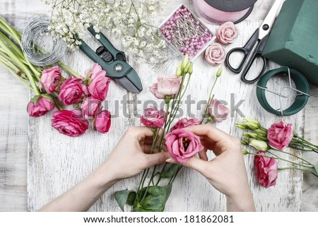 Florist at work. Woman making beautiful bouquet of pink eustoma flowers
