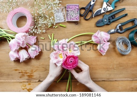 Florist at work. Woman making beautiful bouquet of pink persian buttercup flowers (ranunculus asiaticus) and pink tulips