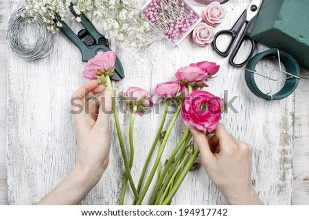 Florist at work. Woman making beautiful bouquet of pink persian buttercup flowers (ranunculus asiaticus)