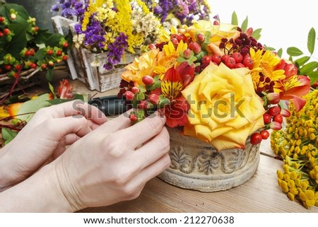 Florist at work: woman making bouquet of orange roses and autumn plants