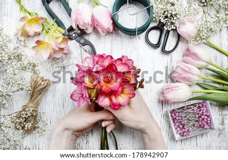 Florist at work. Woman making bouquet of spring freesia flowers