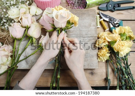 Florist at work. Woman making wedding bouquet of pink roses and yellow carnations